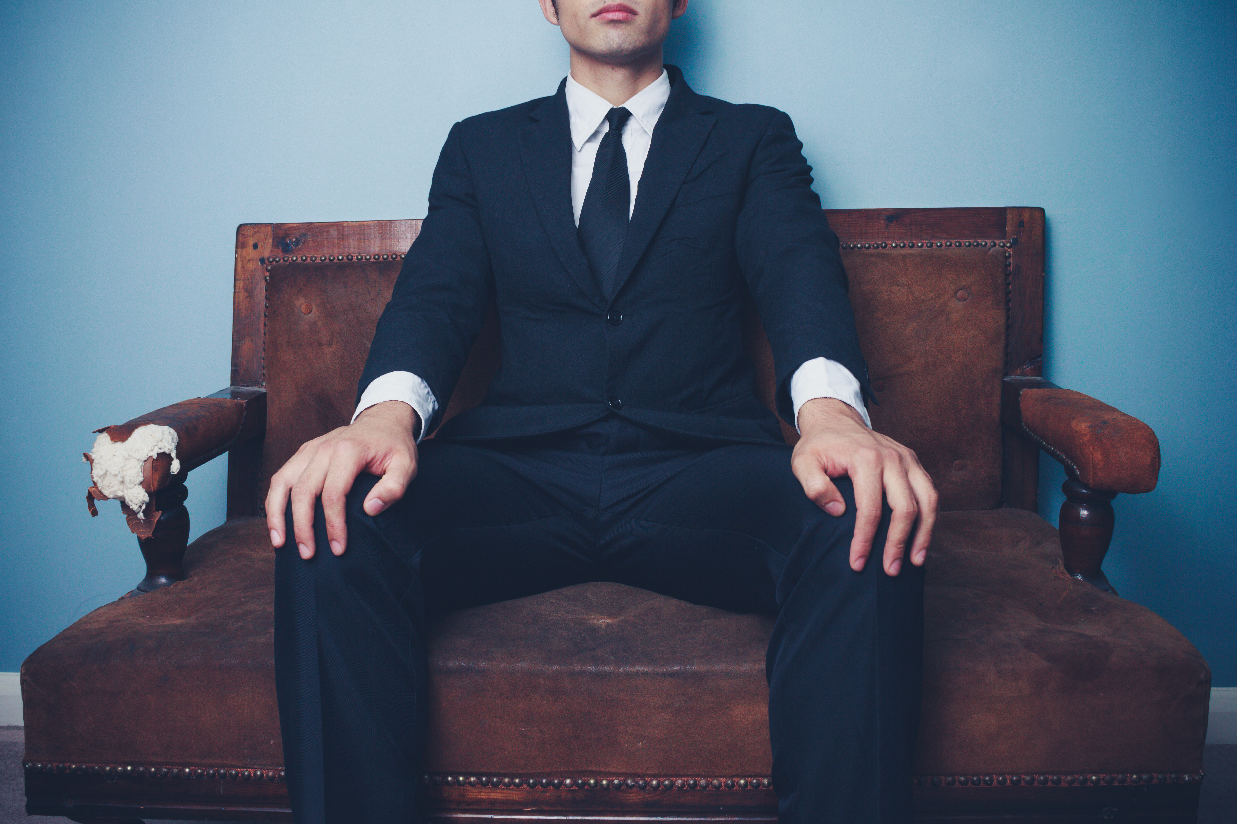 Young businessman on sofa in powerful pose
