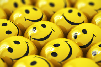 Macro view of happy yellow smiley face ball icons or buttons whith selective focus effect